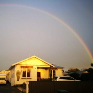 wooden house with a rainbow overhead