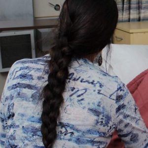 woman with a long dark braid facing away fro the camera
