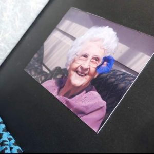 photo album open to a photo of a smiling elderly lady